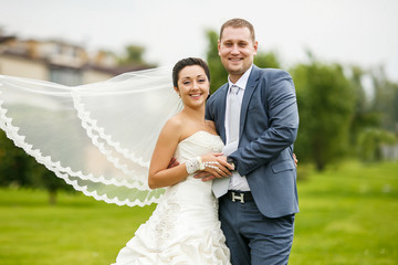Elegant bride and groom posing together outdoors