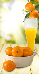 image of juice and tangerines against the sun