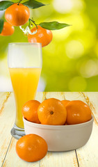 image of juice and tangerines on a green background