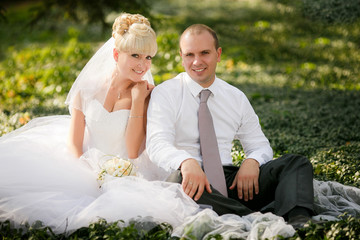 Wedding - Bride and groom  sitting at a green grass