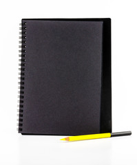 Black paper notebook with yellow pencil isolated on white backgr