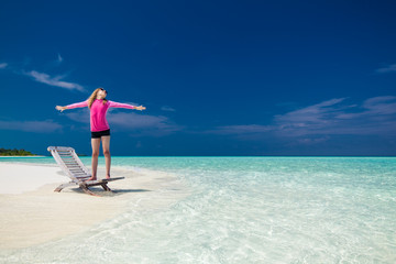 Young girl on a tropical beach with outstretched arms