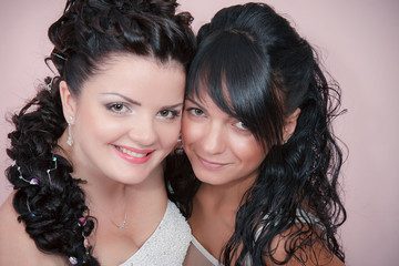 Beautiful bride with her pretty bridesmaid in studio