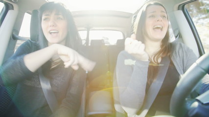 Two beautiful women driving car happy singing