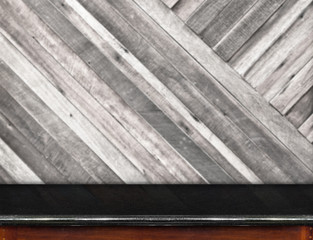 Empty black marble table and blurred diagonal plank wooden wall
