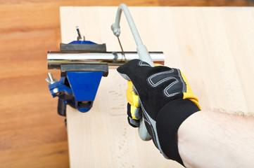 plumber sawing plumbing drain pipe gripped in vice