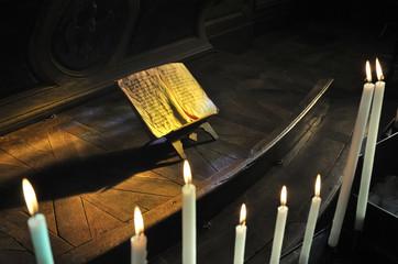 cierges et manuscrit dans une église