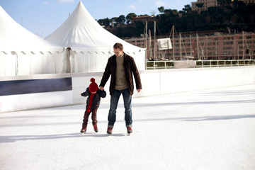 Happy excited little boy and his young father learning ice-skati