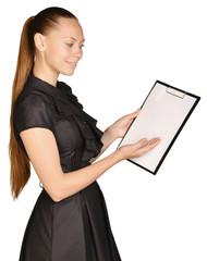 Beautiful girl holding a clipboard in hand and showing blank