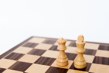 Queen and King wooden chess pieces on a wooden board