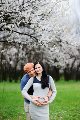 boy and girl on the background of blossoming apricot. A guy hugs