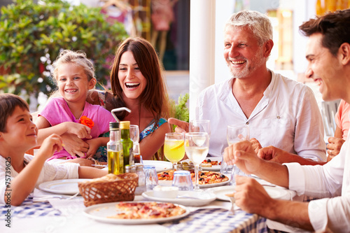Multi Generation Family Eating Meal At Outdoor Restaurant - 75739625