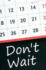 Don't Wait written on a blackboard under a wall calendar