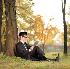 College graduate working on a tablet in park