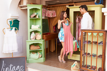 Couple Shopping In Vintage Clothing Store