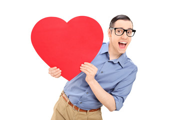 Joyful young man holding a big red heart