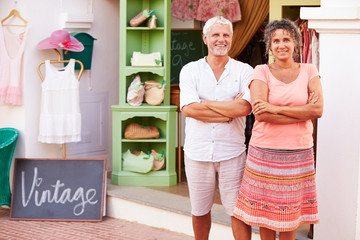 Mature Owners Of Fashion Store Standing Outside Shop