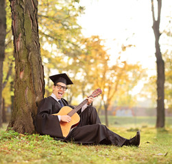 Graduate student playing acoustic guitar in park