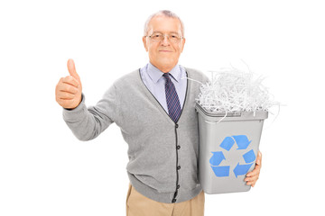 Senior holding a recycle bin and giving thumb up