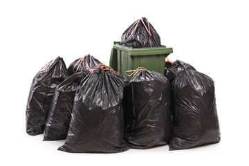 Trash can surrounded by a bunch of garbage bags