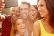 Group Of Friends On Holiday Taking Selfie With Mobile Phone