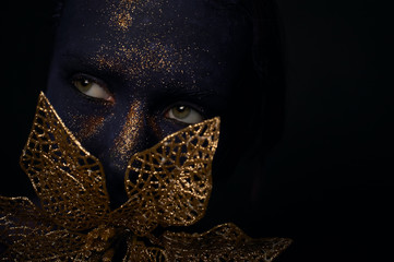 lady with blue face art golden flower in mouth