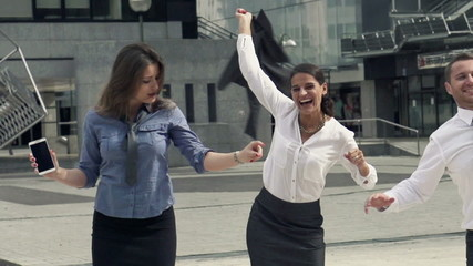 Happy businesspeople dancing in the city,