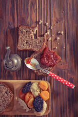 Wholemeal bread with apricot jam surrounded by dry fruit. Vintag