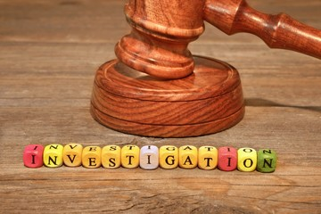 Sign INVESTIGATION and Wooden Gavel