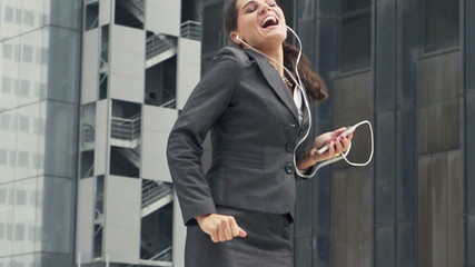 Happy businesswoman listening to music and dancing in the city,