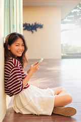 portrait of beautiful teen and mobile phone in hand sitting at h