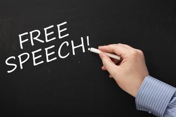 Hand writing Free Speech on a Blackboard with white chalk