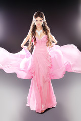 Beauty fashion girl model posing in pink blowing transparent chi