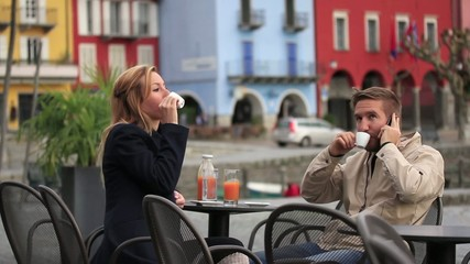 Couple sitting at cafe, man talking on phone