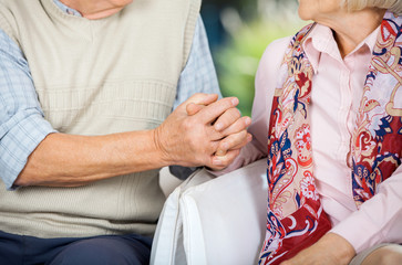 Senior Couple Holding Hands While Sitting On Chairs