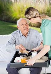 Female Caretaker Serving Breakfast To Senior Man