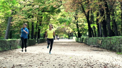 Young girlfriends jogging in park during autumn
