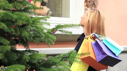 Cheerful woman shopping day dreaming front of window shop