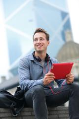Urban man on tablet sitting in Hong Kong