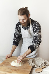 bearded stylish man with apron making dough with white flour