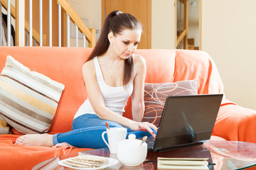 young woman  with laptop on sofa