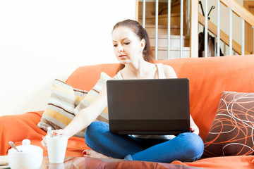 woman with netbook  on sofa