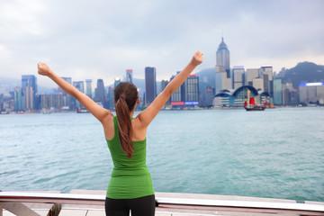 Happy woman success cheering by Hong Kong skyline