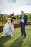 Bride and groom digs the soil on a kitchen garden. Humour. poster