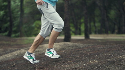 Joggers feet running in forest, slow motion shot at 240fps