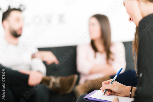 Female psychologist making notes during psychological therapy se - 75758291