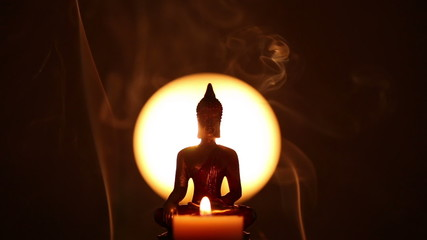 Buddha statue with candle and hand lighting up incense