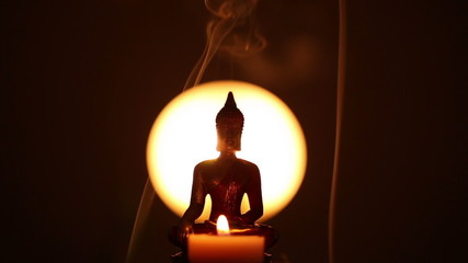Buddha statue with one candle and incense smoke