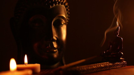 two Buddha statue with candles and incense