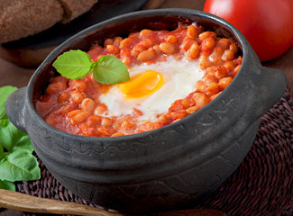 Baked eggs with beans in tomato sauce in the Mexican style